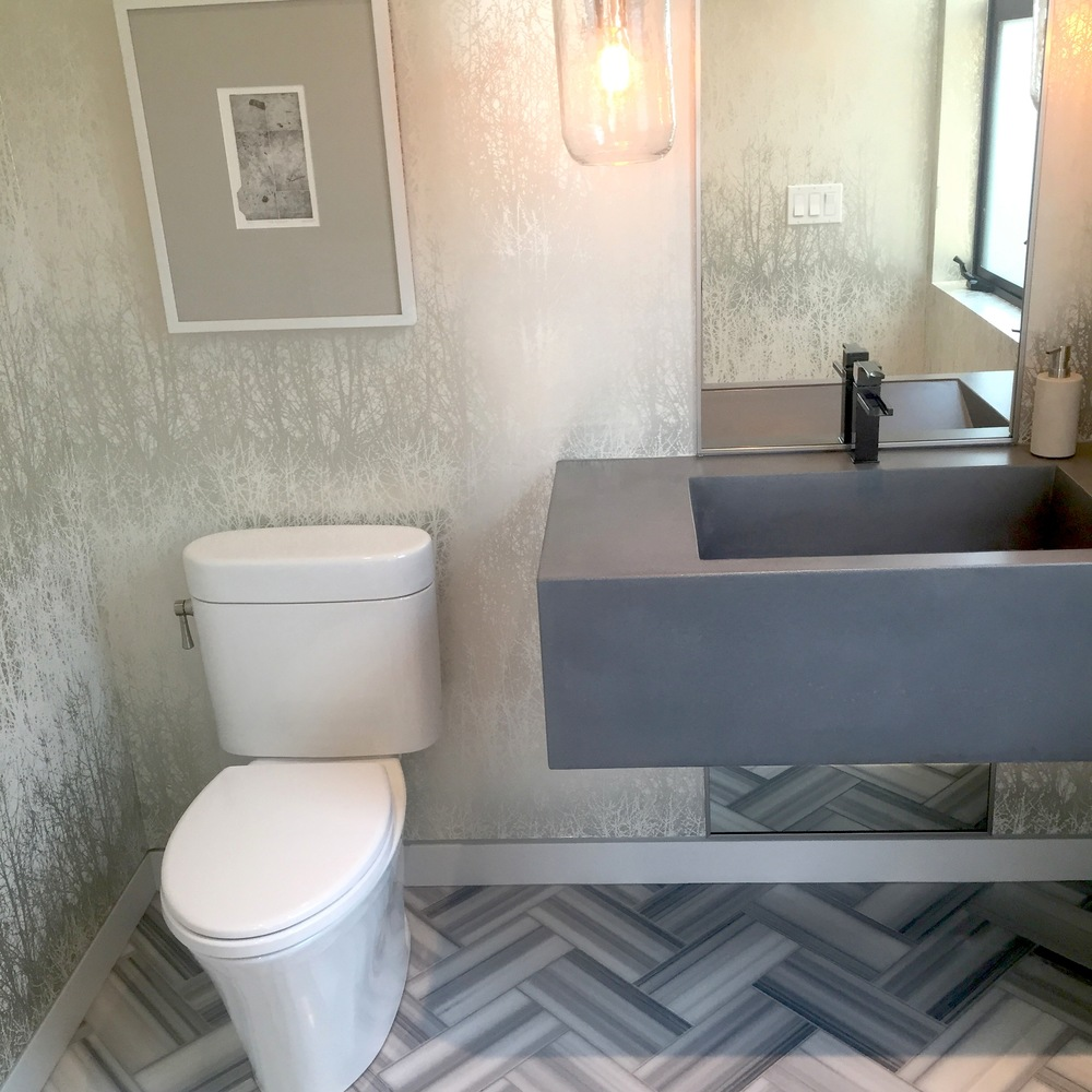 Hit:Nature-themed metallic wallpaper, chevron tile floor patternwith a natural cement -looking sink.