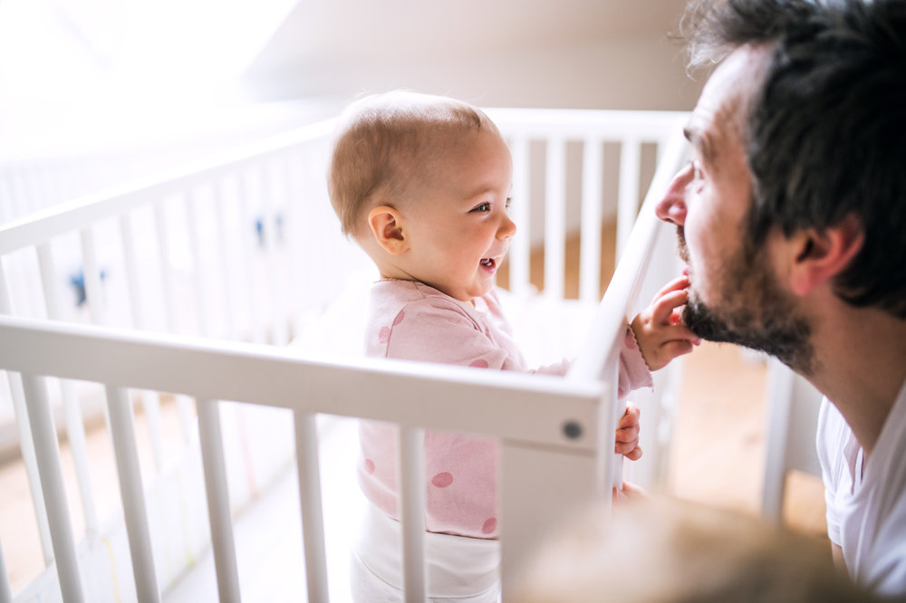 A_small_toddler_girl_standing_in_cot_with_her_father_at_home..jpeg