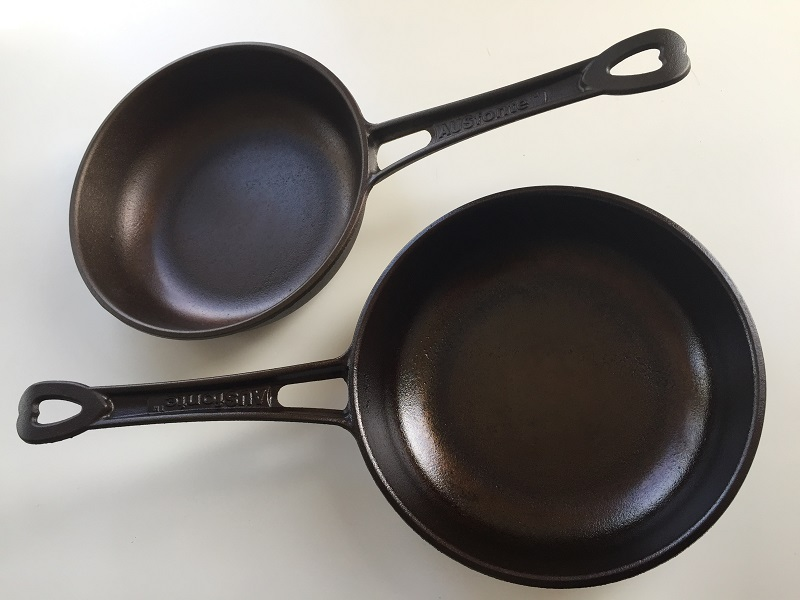AUSfonte 24cm Sauteuse pan with light factory pre-seasoning (top), and after the recommended further 6 seasoning runs (bottom). When the pan is well-seasoned and black, the pits aren't as evident. After much more cooking they fill in and the base becomes perfectly smooth, corrosion-resistant and low-stick.