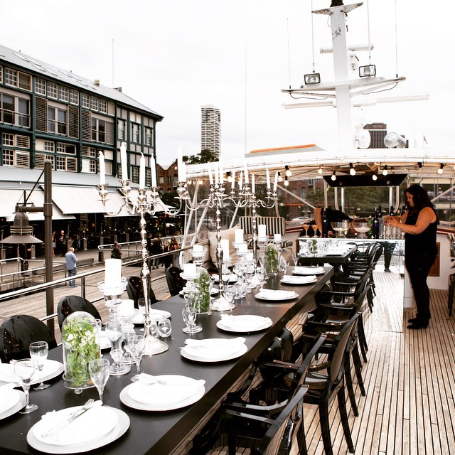 Granted @theboatsydbey is the fricken hottest boat in the harbor.... It was transformed to the highest level thanks to the most incredible and generous set up by @valianthire. This is how we got to dine underneath the harbor bridge 😍! Candlelabra's and a gentle ocean breeze #itdoesntgetbetterthanthis #dininginthespotlight. @rarakittyvintage thanks for the seriously sexy lighting too!