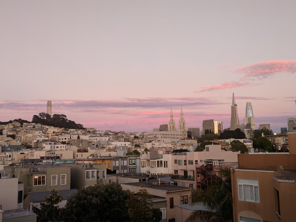 The North Beach neighborhood at dusk with downtown skyscrapers to the right.