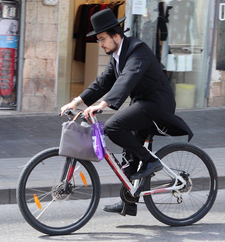 Orthodox Jewish man on a bike in Jerusalem.