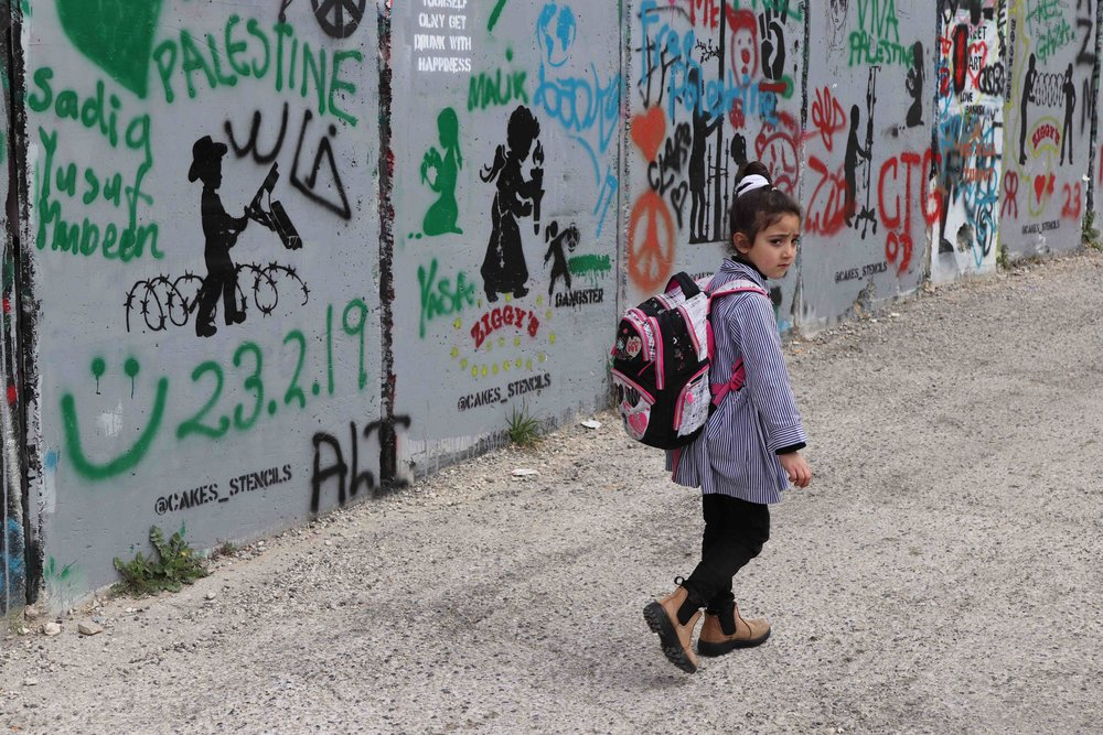 Palestinian girl walks on her side of the barrier wall in Bethlehem.