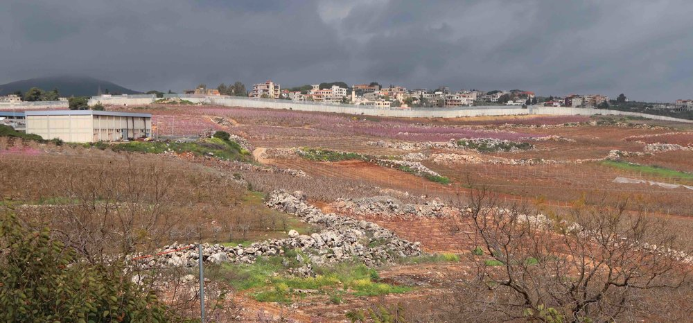 An Israeli security wall separates fertile farmland from sometimes hostile forces in Lebanon.