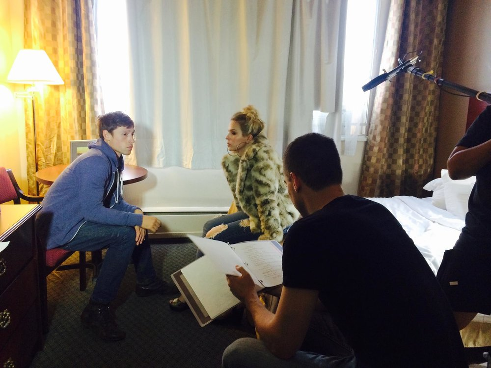 Kris Nielsen directs lead actors Garrett Black and Emma Barratt in the hotel room.