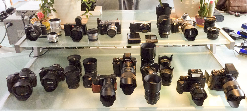 Top Shelf Left to Right - Olympus OM-D E-M10,  M.Zuiko 14-42mm EZ electronic pancake zoom lens, Olympus M.ZUIKO DIGITAL ED 75mm 1/1.8 Lens Olympus M.ZUIKO DIGITAL ED 45mm 1/1.8 Lens, Leica T, Leica Vario-Elmar-T 18-56mm f/3.5-5.6 ASPH Lens, Fuji X100s, Fujifilm TCL-X100 Teleconverter, Fujifilm TCL-X100 Wide Angle Conversion Lens, Nokia Lumia 1020 Smartphone, Blackberryt Q10 Smartphone, Samsung Galaxy 2 camera, Nikon Df, Sigma 35mm f/1.4 A DG HSM ART lens (Nikon fit), Nikon 28-200mm f/3.5-5.6 AF-G, Nikon 24-85mm AF-S G, Nikon 100mm f/2.8 Series E, Voigtländer 20mm f/3.5 SL-II Aspherical.  Bottom Shelf Left to Right - Panasonic FZ1000, Sony RX10, Sony a6000, Sony A7r, Sony 10-18mm f/4 OSS Lens, Sony 55mm f/1.8 Sonnar T* FE ZA Lens, Sony FE 35mm F2.8 ZA Carl Zeiss Sonnar T*, Sony 85mm f2.8 SAM Lens, Sigma 35mm f/1.4 A DG HSM A Lens (Sony a-mount fit) Voigtlander APO-LANTHER 90mm F3.5 SL II, Sony LA-EA4 a-mount to e-mount adapter, Fuji X-E2. Fuji X-T1, Fujifilm XF 55-200mm f/3.5-4.8 R LM OIS Fujinon Lens, Fujifilm XF 10-24mm f/4 R OIS Fujinon Lens, FUJINON LENS XF18-55mmF2.8-4 R LM OIS, FUJINON XF14mm F2.8, Fujifilm XF 23mm f/1.4 R Fujinon Lens, FUJIFILM XF 56MM F/1.2 R, Fuji 18-135mm f3.5-5.6 WR LM R OIS Fujinon Lens, Fujifilm EF-X20 Flashgun.  IMAGE TAKEN WITH iPAD AIR. Another camera.