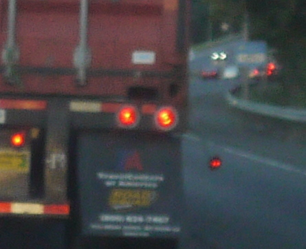 Driving home I got stuck behind this truck carrying a cargo container. One of the little running lights on the passenger side was flailing on its wire in the truck's own wind, but still lit up.