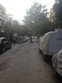 A security guard walks across the street, near the guest house in Saket