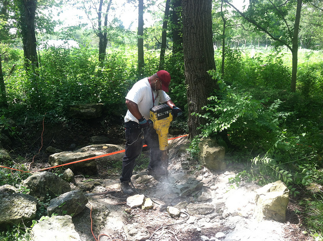 Tomaz Williams breaking apart the concrete liner of the original pond (photo by Sara Black)