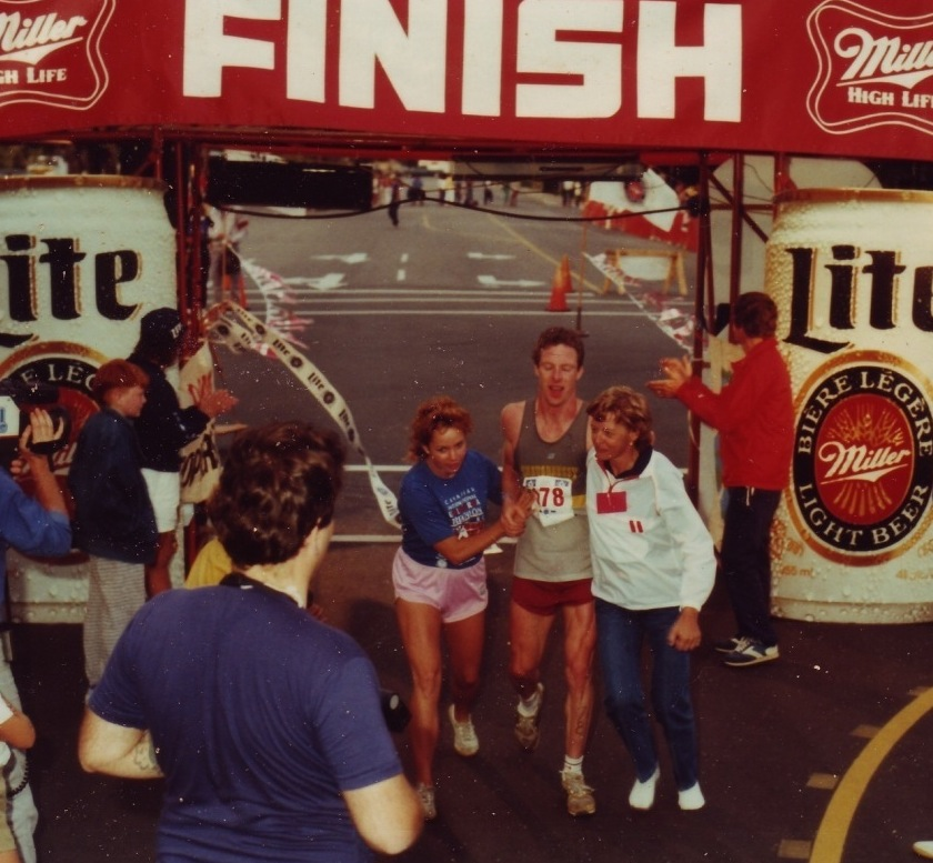 Kay Rhead helps an athlete across the Ultra finish line, August 1985
