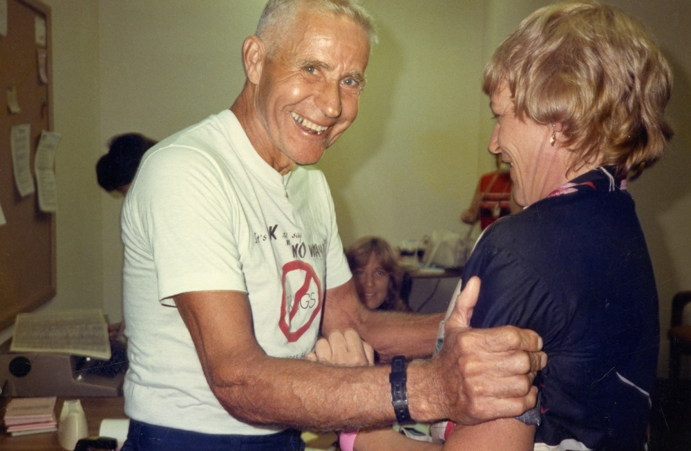 Ironman Edson Sower, shown here at age 70, embraces Ironman race director Kay Rhead.