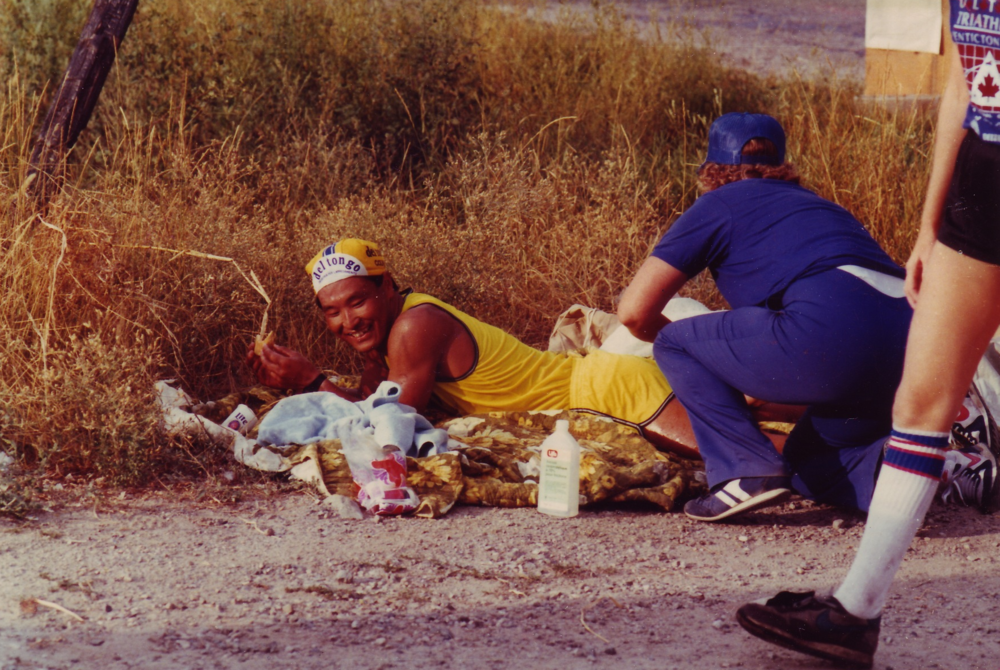 An athlete gets a leg massage from an aid station volunteer on the run course.