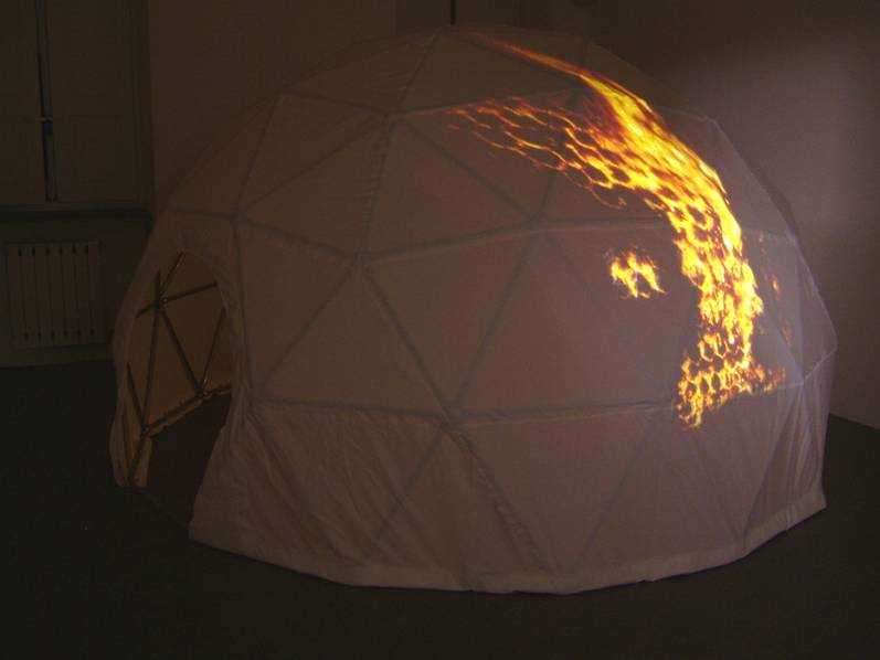 With the demise of Buckminster Fuller's pavilion serving as the central episode, the viewer is invited to enter  Spirit of 76 , a 2m-tall geodesic dome. The white dome seems the quiet and hopeful emblem of Utopian architecture, only to reveal a surface marred by a projected image of the pavilion engulfed in flames. Inside hangs a mobile constructed of celestial symbols physically extruded from various national flags, inspired by the protestors who removed the stars from the American flag during President Lyndon Johnson's visit to Expo 67, an episode recounted in an adjacent drawing.