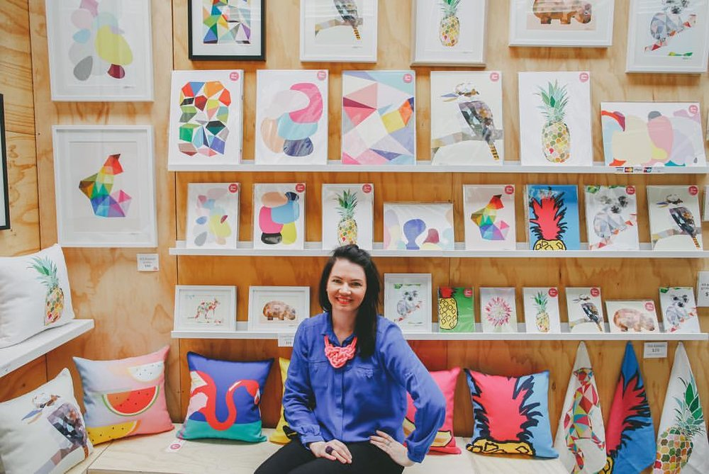 Susie surrounded by prints and cushions at Rose St Artists' Market.