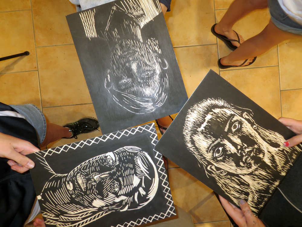printmaking students showing off their woodcut self portraits les tapies summer programs