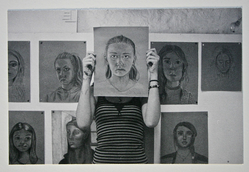 a student with her self portrait drawing