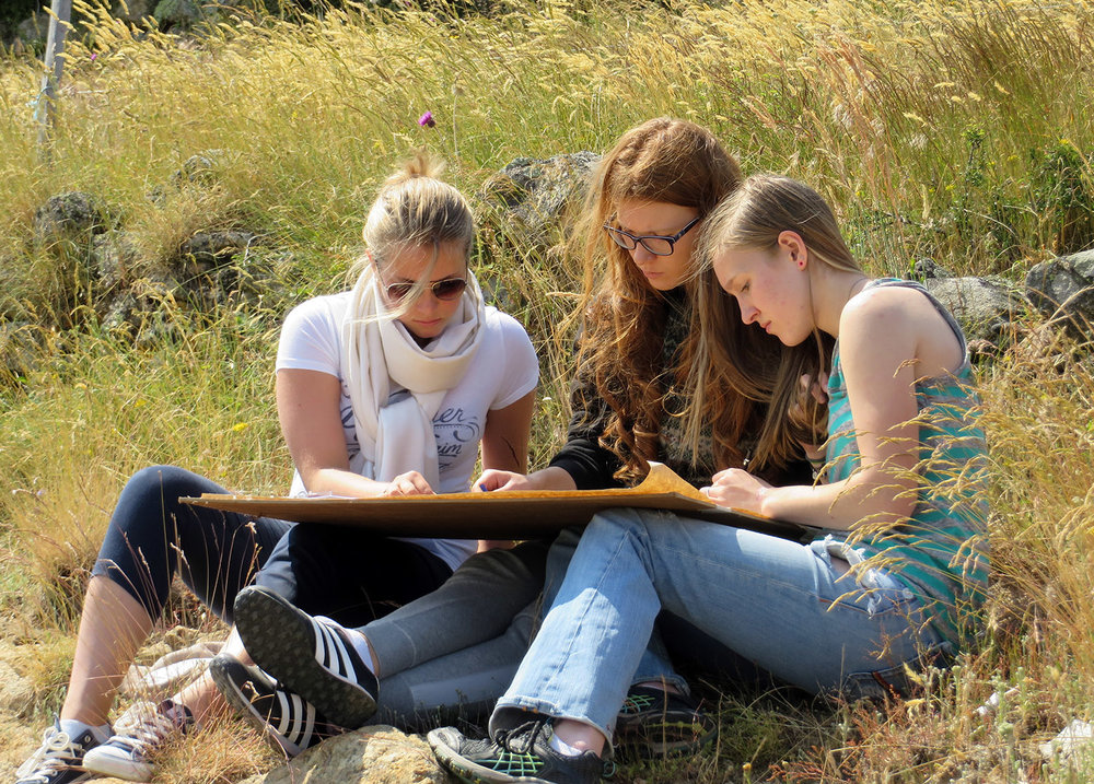 high school students drawing and painting in the landscape