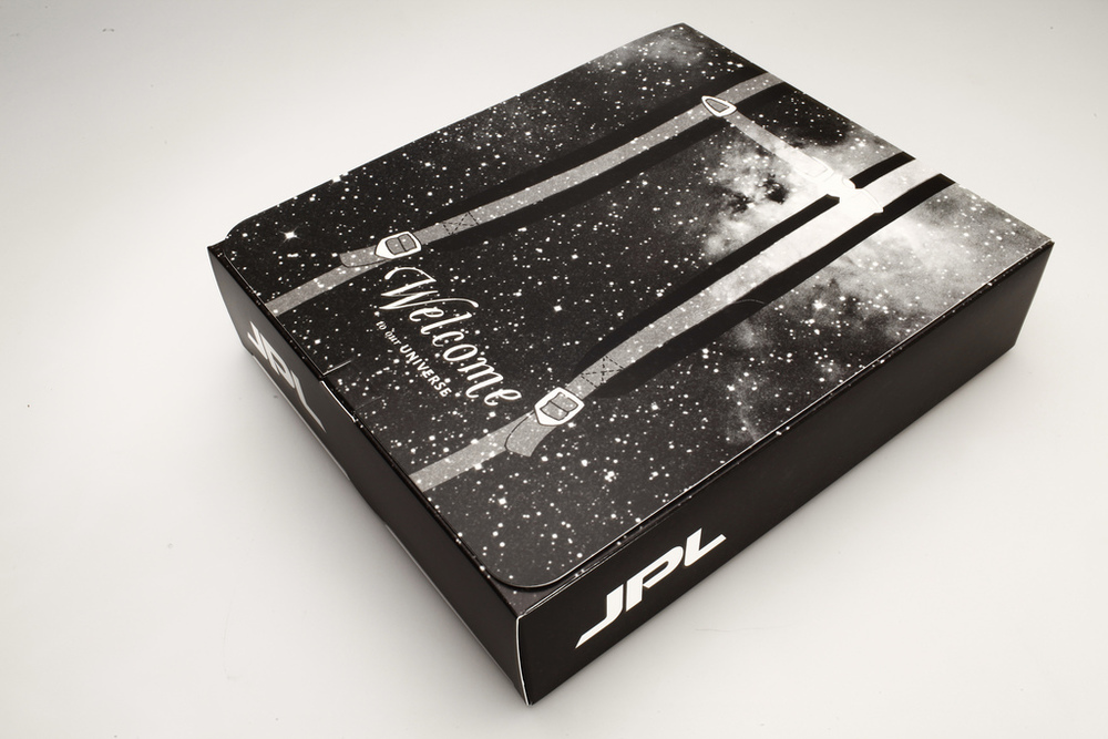 "The Jetpack Box reads,  ""Welcome to Our Universe"" on the outside, and on the inner flap, ""Here's your Jetpack"". The box features an illustration of a Jetpack with backpack straps that wrap around to the reverse side, as shown here."