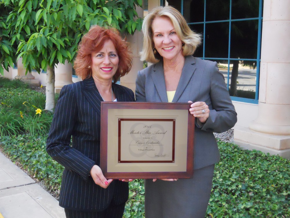 Renee Grubb (right), of Village Properties, hands Cimme Eordanidis her Star Mentee award.