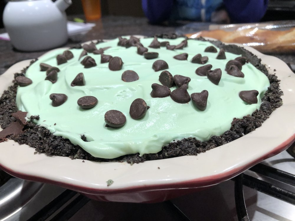 Mint whipped cream, pudding, and chocolate with Oreo crust pie.
