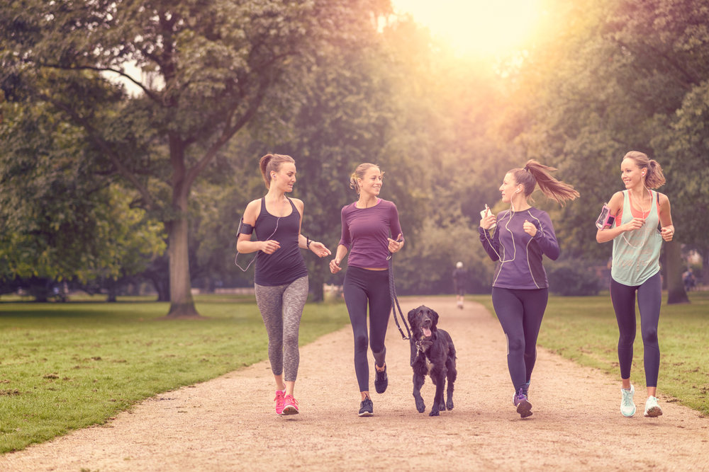young women running as group with dog