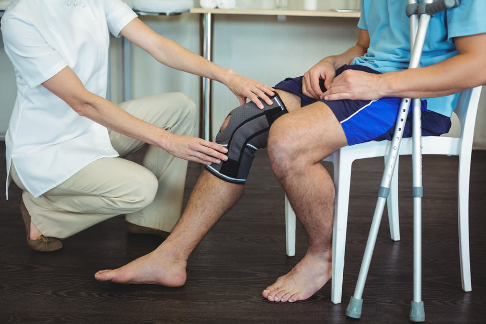 therapist adjusting knee brace on patient.jpg