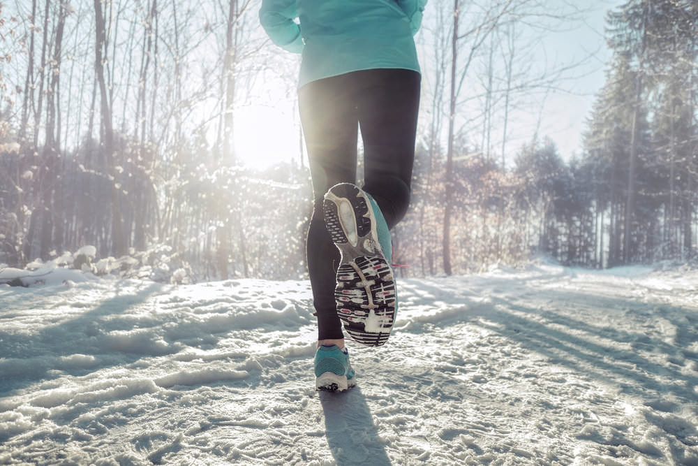 woman running on snowy trail in sunlight.jpg