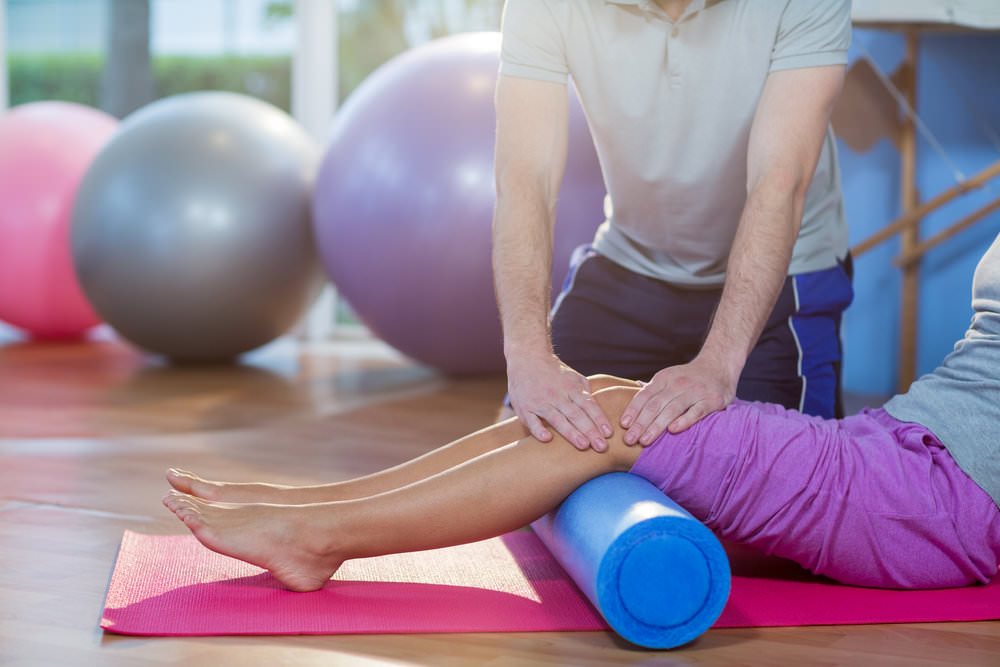 Physiotherapist assisting woman while exercising on exercise mat.jpg