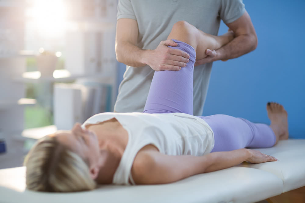 Male physiotherapist giving knee massage to female patient.jpg