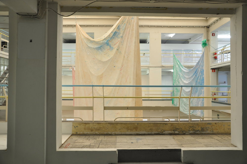 SKINS AND SHEETS, experiments on various types of sheets, hanging in the open structure of an old car-garage. The sheets can be viewed from three different levels - Plastic sheets, pigments, paint, rope, wood, 20 x 20 x 20m, Sint Lucas Antwerp, 2016