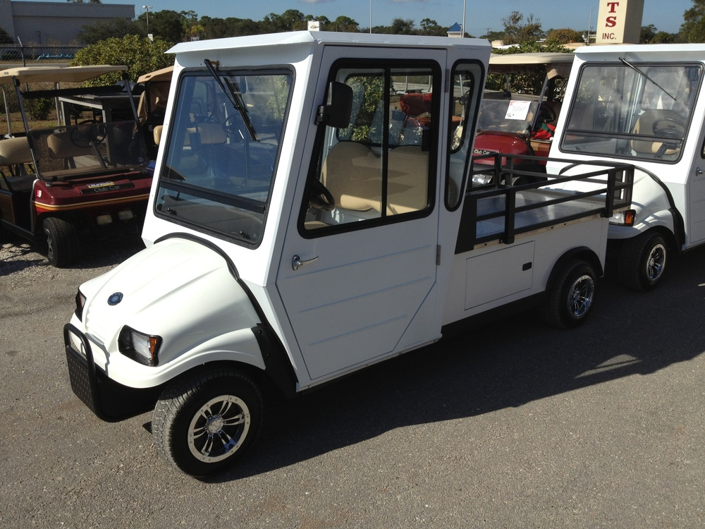 "2 passenger utility vehicle with a hard enclosure and  a 48"" x 60"" x 10"" stake bed cargo area."