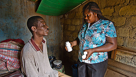Agnes Onydo conducts a home visit with Jayo Benjamin. Since he lost his sight, he needs help around his home and to stick to his HIV drug regimen. Photo by Karen Kasmauski for CRS.