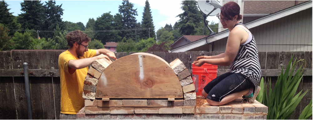 Stephen Ruby and Becca Headline helping build the wood-fired pizza oven at Ceramistas Seattle.