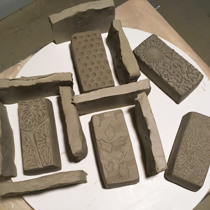 "Green clay formed into ""brick"" shape- ready to be cast"