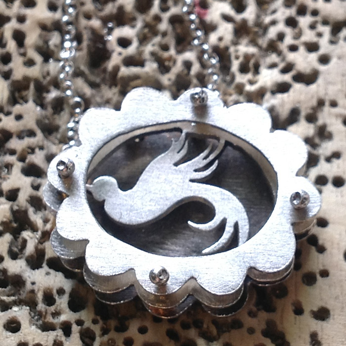 Small scalloped shadowbox necklace with swallow.