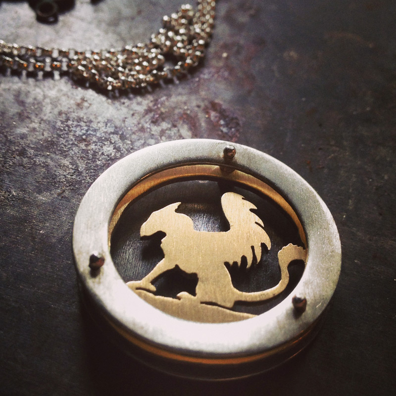 Large circle shadowbox necklace with 10k gold griffin as center design and gold fill chain.