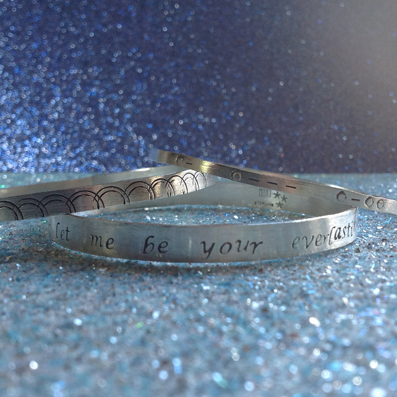 Gift set of three hand stamped sterling silver bangles. One with song lyrics, one with geometric design and one with braille coding.