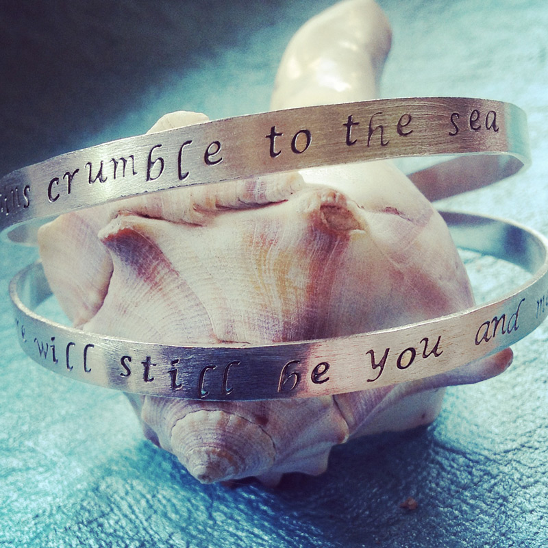 Set of two hand stamped sterling silver bangles with song lyrics.