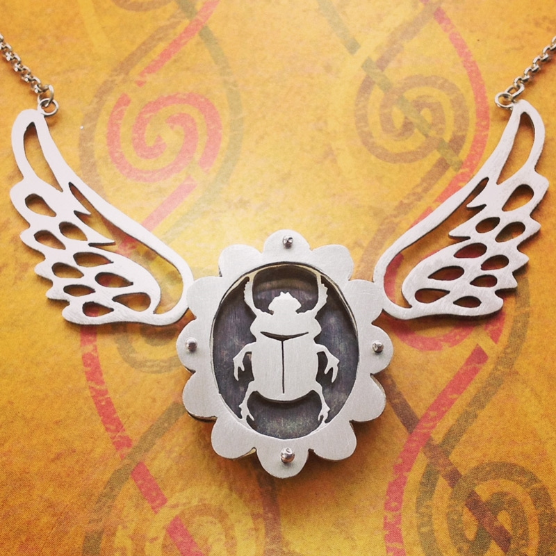 Large scalloped shadowbox necklace with scarab and sterling wings.