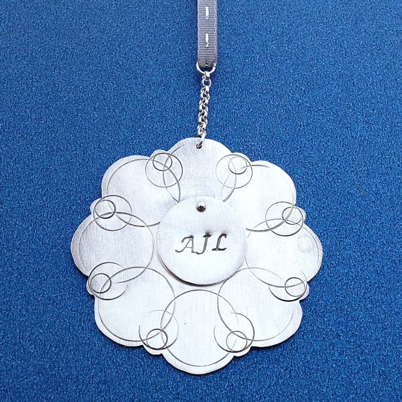 Nickle ornament with stacked sterling disc and stamped initials.