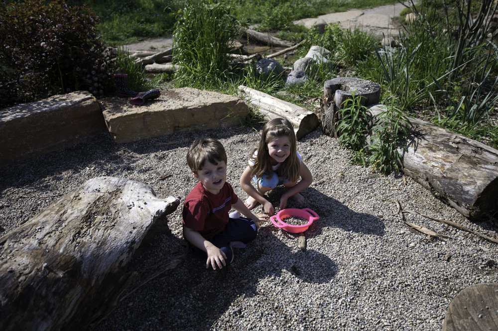 Rudimentary boulders and natural logs offer bounded destinations with loose natural materials, such as dig pits of pea gravel and sand. Some pits are located in the woods, where pre-school children and parents can be protected from the sun.