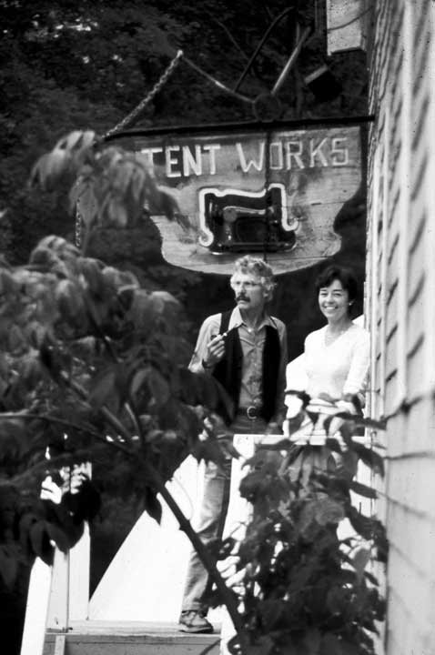 "Marilyn and Bill Moss stand under the first company sign, ""Tent Works,"" which included an old Singer sewing machine. Tent Works Ltd. was established in Camden, Maine in 1975."
