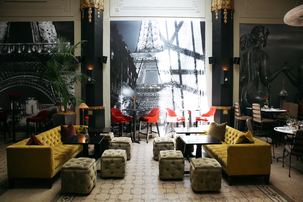The decor at Le Petit Paris has neutral, rich tones with pops of red and a distinct art deco style.