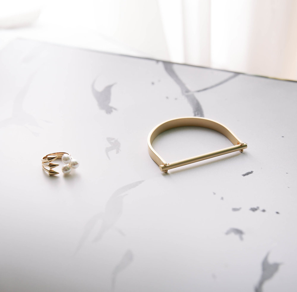 The Colby bracelet and pearls at hand ring, both in gold.