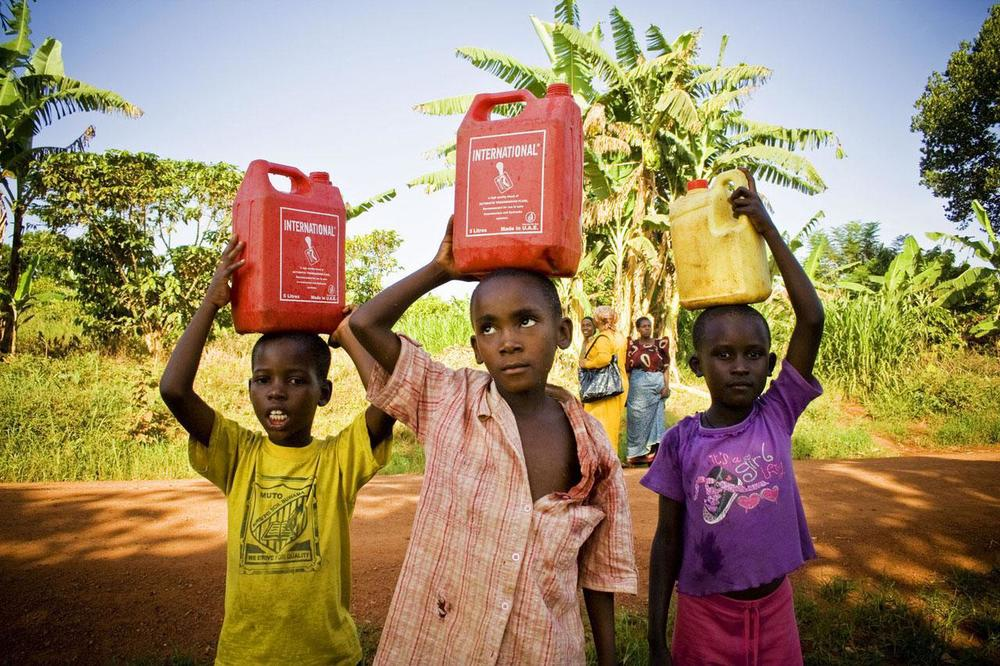 Homeward bound in the district of Buikwe, Uganda, boys transport water on their heads from a well.