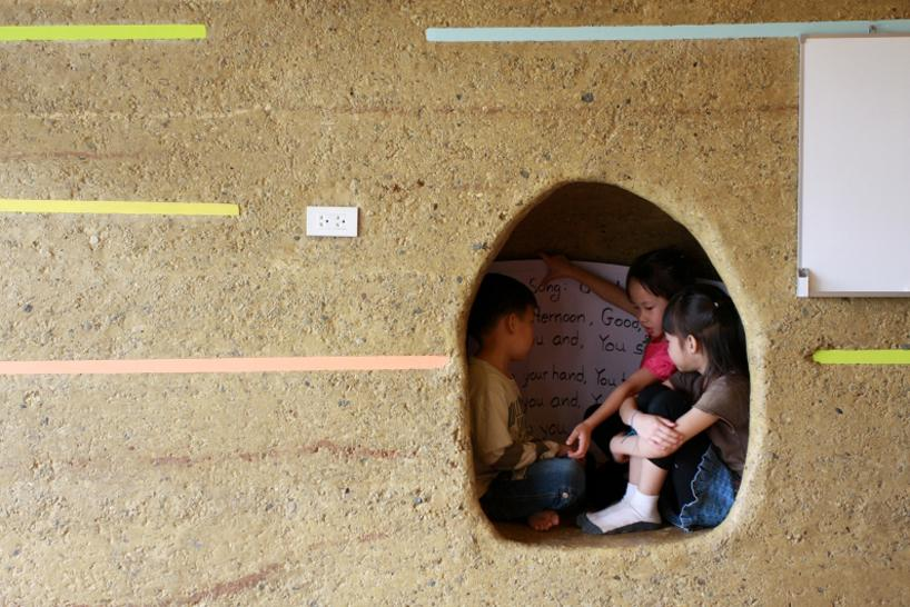 Students spend time in one of the cutouts in the pavilion's adobe walls, where the curves of the roof and these interior cutouts mimic the silhouettes of the neighboring mountains. Children's innate knowledge is respected by the school's holistic mindset. Photo courtesy of Ally Taylor/Panyaden.