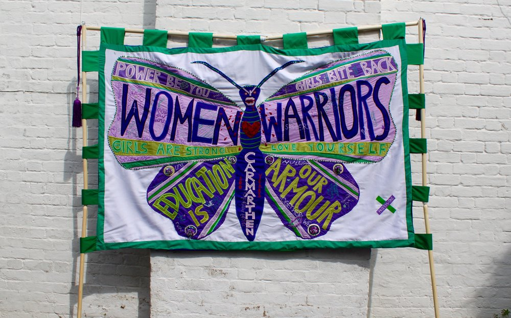"In March, I was privileged to be asked by Oriel Myrddin Gallery, Carmarthen to work as the lead artist on a community project at Dr M'z youth centre to mark the 100 year centenary of the women's right to vote, in designing and making a banner, flags, and sashes for a mass participation artwork on June 10th called ""PROCESSIONS 2018"", produced by Artichoke with National Heritage Lottery support.   We came together in workshops to discuss what being a strong woman means and brainstorming ideas through drawings and collage before voting on a final design, The Butterfly Warrior. We shared embroidery skills and stories, and worked together on adorning our butterfly with tattooed  embroidered messages.   To see more of our journey, head over to  https://www.instagram.com/omp2018_/"