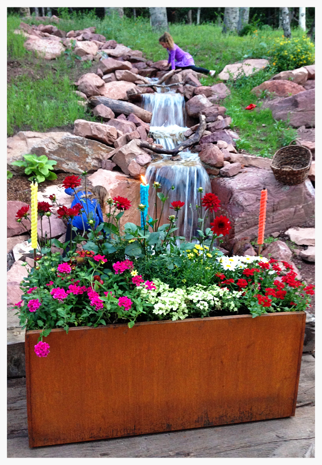 Above: one of several steel planters that the homeowners rusted, by drenching in a vinegar solution, sits at the entry while a young girl played next to the water feature.    Just below: Colorful pillows, tablecloths and sunflowers brighten up neutral backgrounds of stone and textiles.