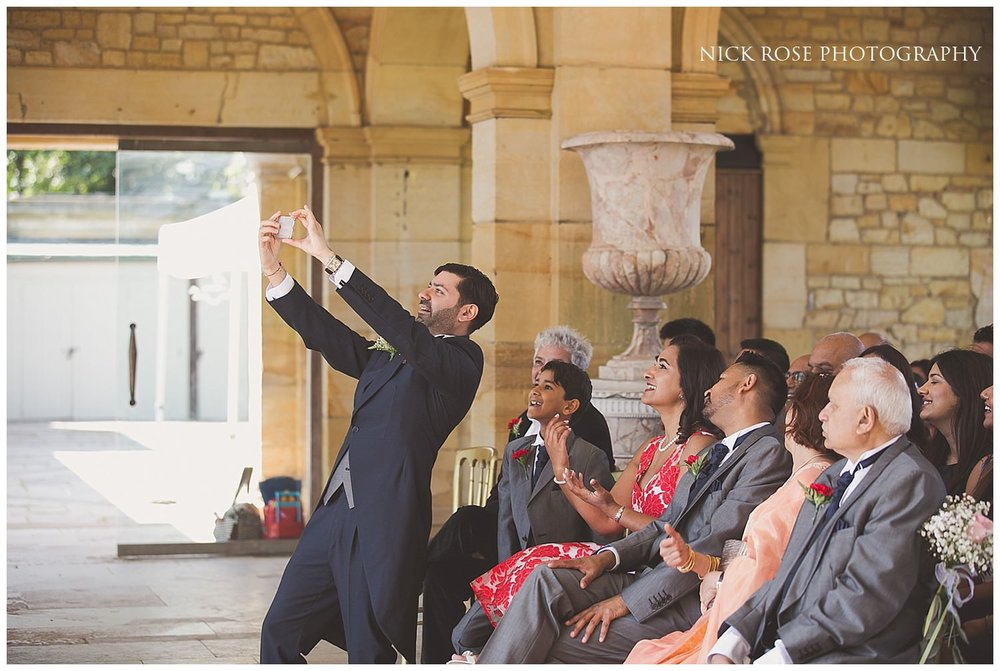 Groom taking a selfie with guests before a Kent wedding ceremony