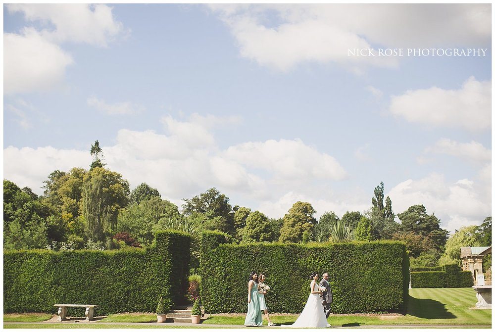 Bride walking across the gardens before a Hever Castle wedding ceremony in Kent